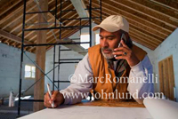 Picture of a hispanic architect working on a set of blue prints and talking on the phone. He is wearing a baseball cap and has a beard.